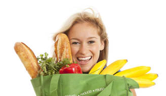 Close-up of young woman with green recycled grocery bag of healthy food and vegetables