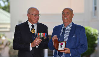 Governor-General David Hurley (L) presents the Victoria Cross to Garry Ivory, nephew of Ordinary Seaman Edward 'Teddy' Sheean on the 78th anniversary of his death while trying to save his shipmates during World War II, in Canberra, Tuesday, December 1, 2020. (AAP Image/Mick Tsikas) NO ARCHIVING