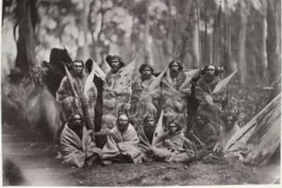 group of aborigines sitting and standing whole length full face wearing animal skins some holding weapons image state library of victoria