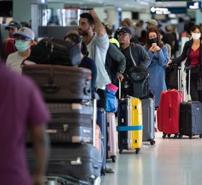 Travellers queuing to check in for their flights at the Sydney International Airport, Sydney, Friday, March 27, 2020. The Australia Federal Government have introduced strict social distancing rules in an effort to contain the COVID-19 Coronavirus pandemic.(AAP Image/James Gourley) NO ARCHIVING