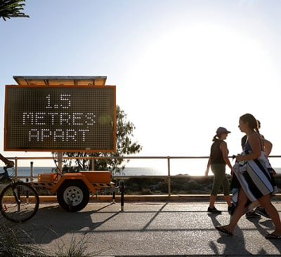 Members of the public are seen walking past a sign reading