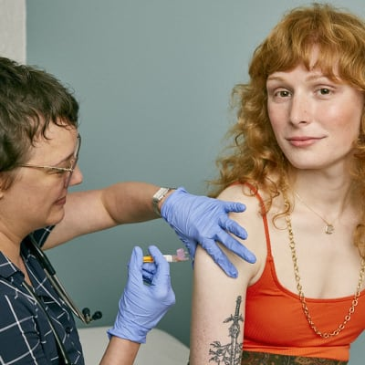 Woman receiving a vaccine in a doctor