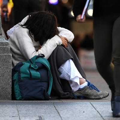 A homeless woman sits on a street corner in central Brisbane, Friday, June 9, 2017. (AAP Image/Dan Peled) NO ARCHIVING