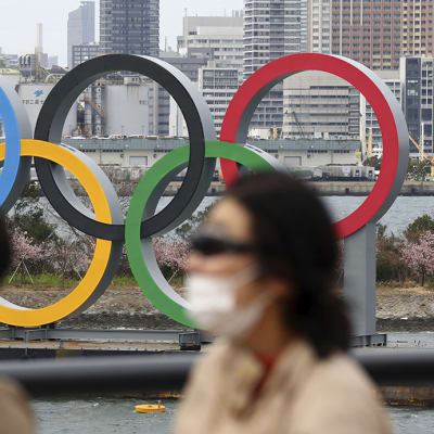 People wearing a mask walk near the Olympics