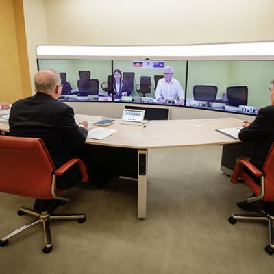 L-R foreground: Secretary of the Department of Prime Minister and Cabinet, Phil Gaetjens, Australian Prime Minister Scott Morrison and Chief Medical Officer Professor Brendan Murphy, speak with NSW Premier Gladys Berejiklian (on screen) during a National Cabinet meeting to discuss COVID-19 (coronavirus), from the teleprescence room of Parliament House in Canberra on Sunday 22 March 2020. (AAP Image/Sydney Morning Herald, Pool Alex Ellinghausen) NO ARCHIVING