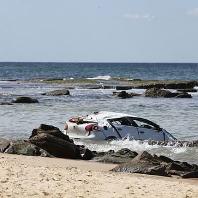 The scene where a car plunged off a cliff at Bar Beach in Newcastle, Thursday, September 24, 2020. Two women and a child have been injured after a car drove off a cliff and crashed onto a beach in Newcastle today. (AAP Image/Darren Pateman) NO ARCHIVING