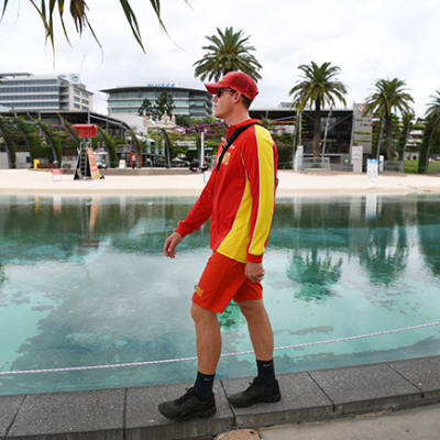 A lifeguard patrols the parameter of South Bank beach which has been closed to the public in Brisbane, Wednesday, March 25, 2020. A shutdown of non-essential services as well as domestic and international travel restrictions are in effect Australia wide in a bid to slow the spread of the COVID-19 coronavirus. (AAP Image/Dan Peled) NO ARCHIVING