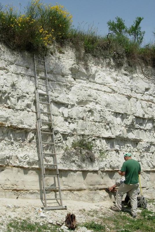 base dei sedimenti lacustri biancastri del MIS 19c con i livelli di ceneri vulcaniche datati (strati sottili arancioni) che ne hanno permesso di ottenere un preciso quadro cronologico della successione e i ricercatori al lavoro