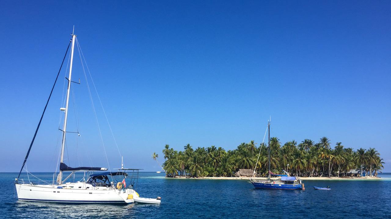 Barco a vela e pesqueiro em frente a ilha paradisíaca