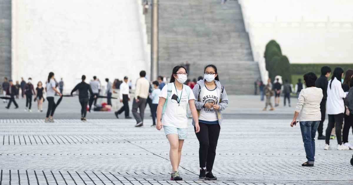 两个女孩穿着面部面具和社会距离,而在镇上出来