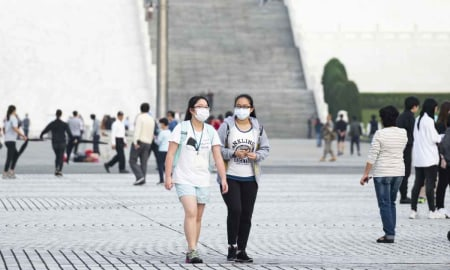 Two girls wear face masks and social distance while out in town