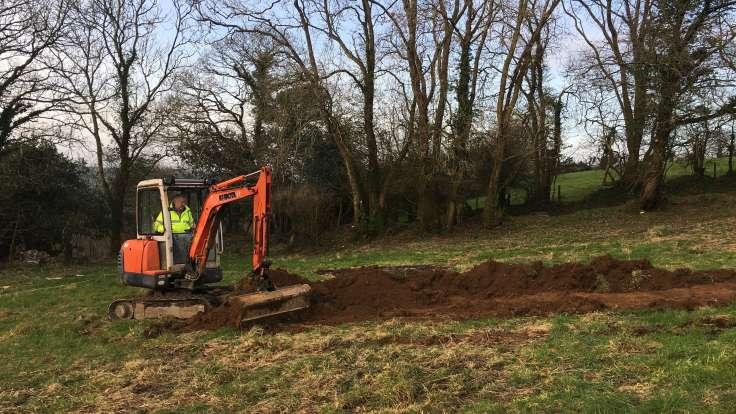Man in mini-digger, scraping the top soil