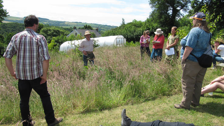 Man in hat with pouch (not paunch) standing in the long grass, talking with a circling group of permaculturalists, polytunnel, house and hills in the background.