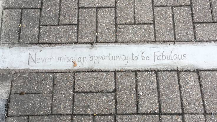 Photo of pavement with words scratched into concrete 'Never miss an opportunity to be Fabulous'