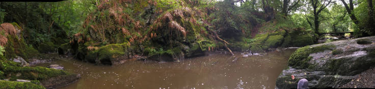 Panorama of steep sided small river from the waterfall, trees to the left, bridge to the right