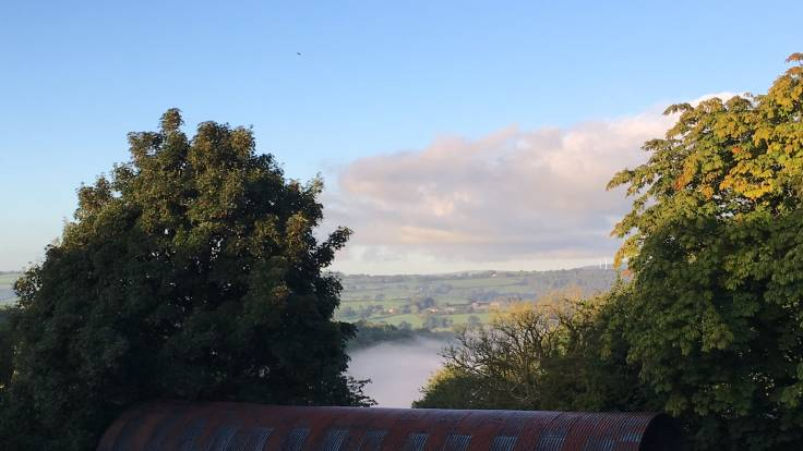 View over barn roof, through trees to misty valley