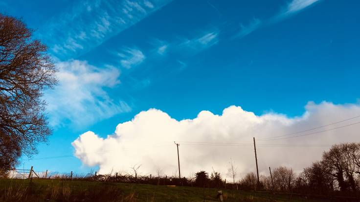 Big white cloud, blue sky, fence, telegraph poles