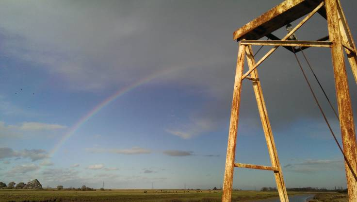 Rainbow over marsh, top of rusted metal footbridge visible