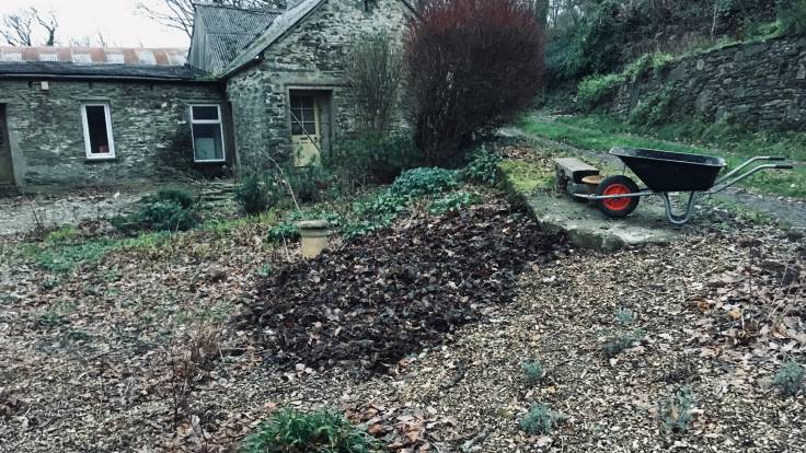 Wheelbarrow above flower bed on a slope, covered in leaf litter mulch