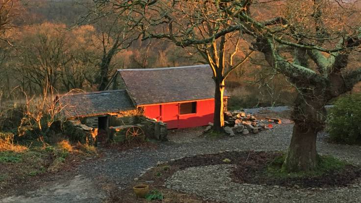 Carthouse with red door and stone pigsty in evening sun