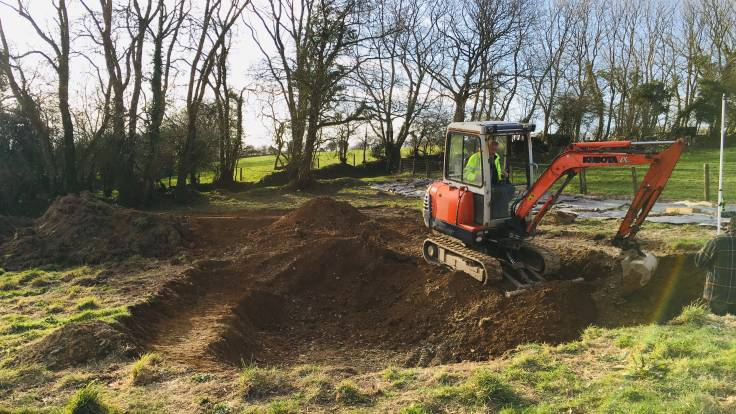 Orange mini-digger digging pond in field