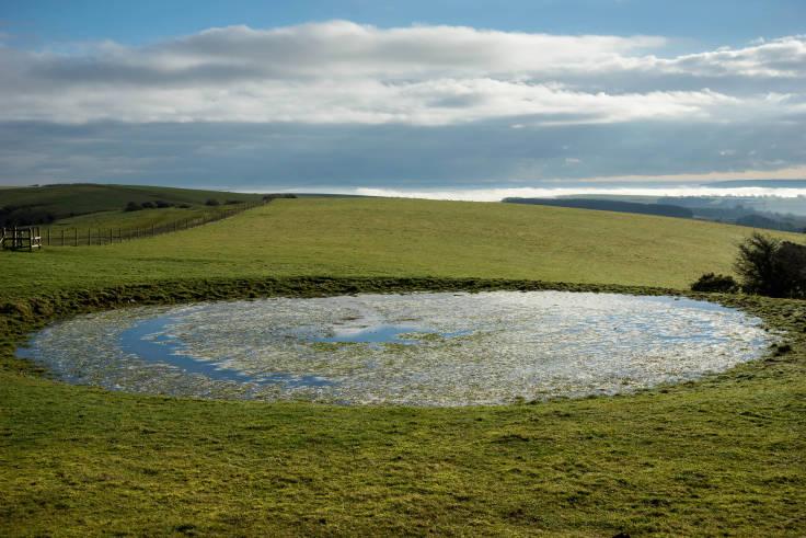 Circular dew pond in rolling chalk hills