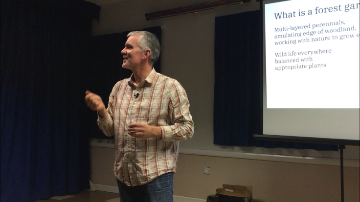 Man in checked shirt giving talk in front of screen