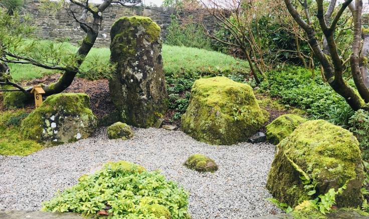 Moss covered stones by dry gravel Japanese Garden