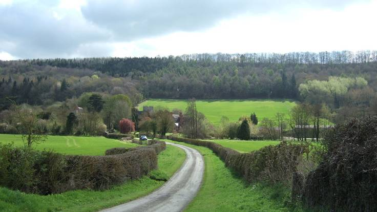 Country lane through wooded & pasture valley