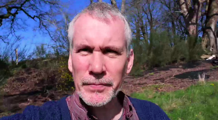 Middle aged man squinting through the sun into the mobile phone camera
