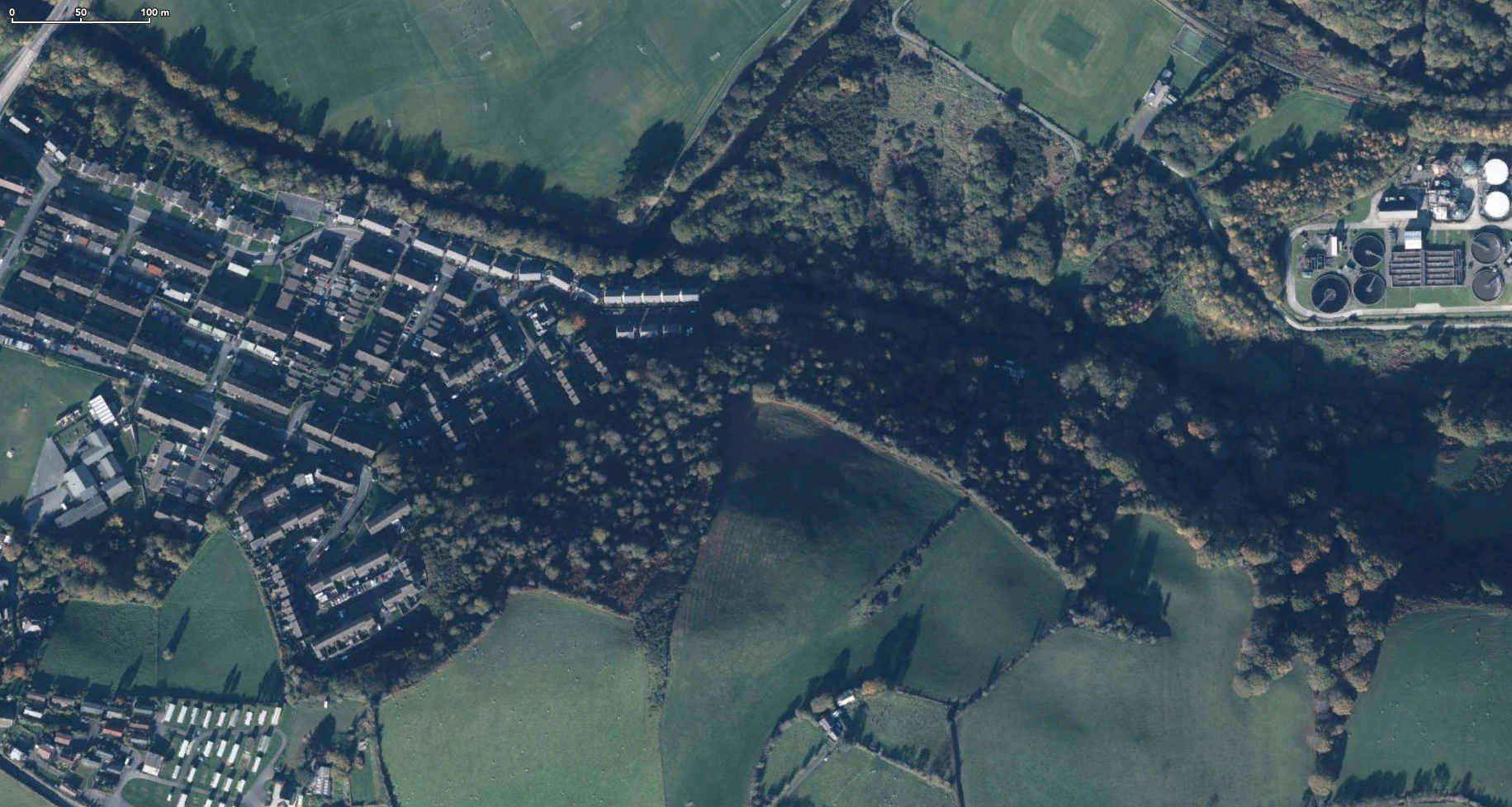 Satellite photo of wooded area at edge of town