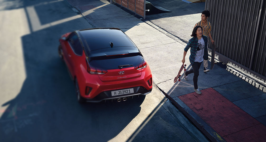 veloster-js-liveloud-car-left-side-rear-top-view-red--beside-persons