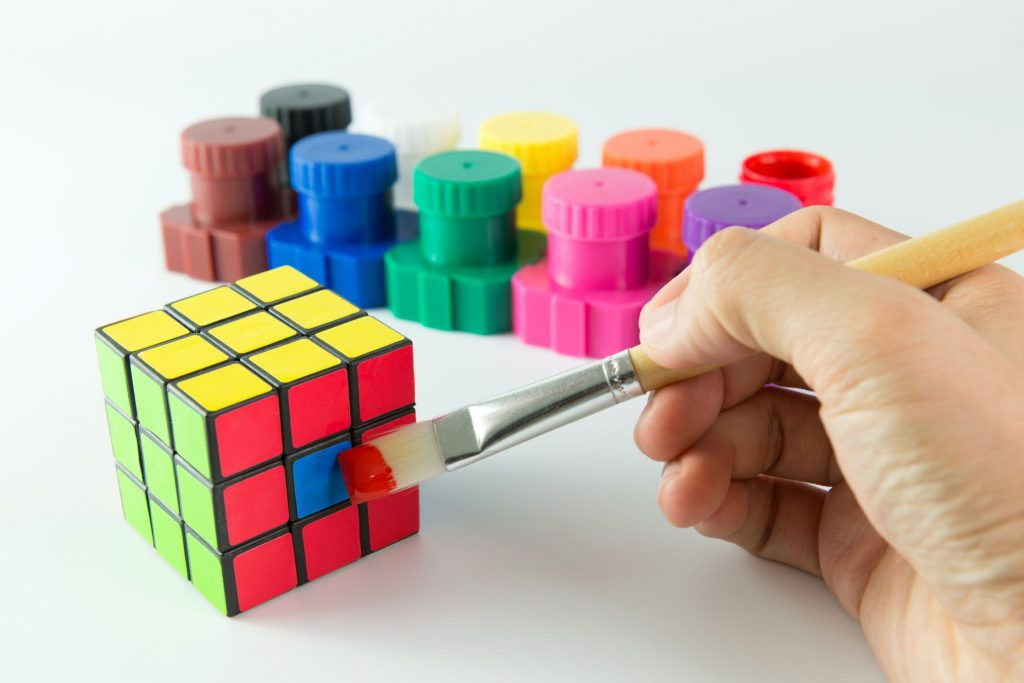 Person cheats to complete a rubik cube by painting a blue square red to emphais how attempting to shortcut the process of adopting okrs was a mistake.