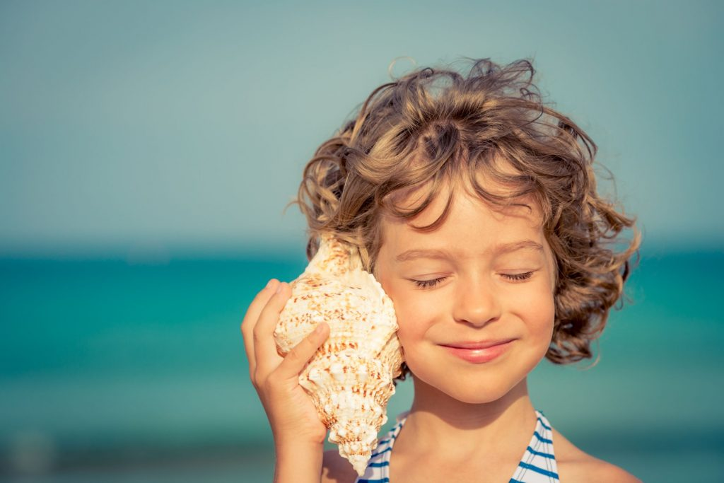 Child listens to a conch shelf to emphasis the need to listen and learn during the process of adopting OKRs