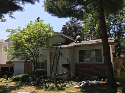 roofers installing shingles on split level house