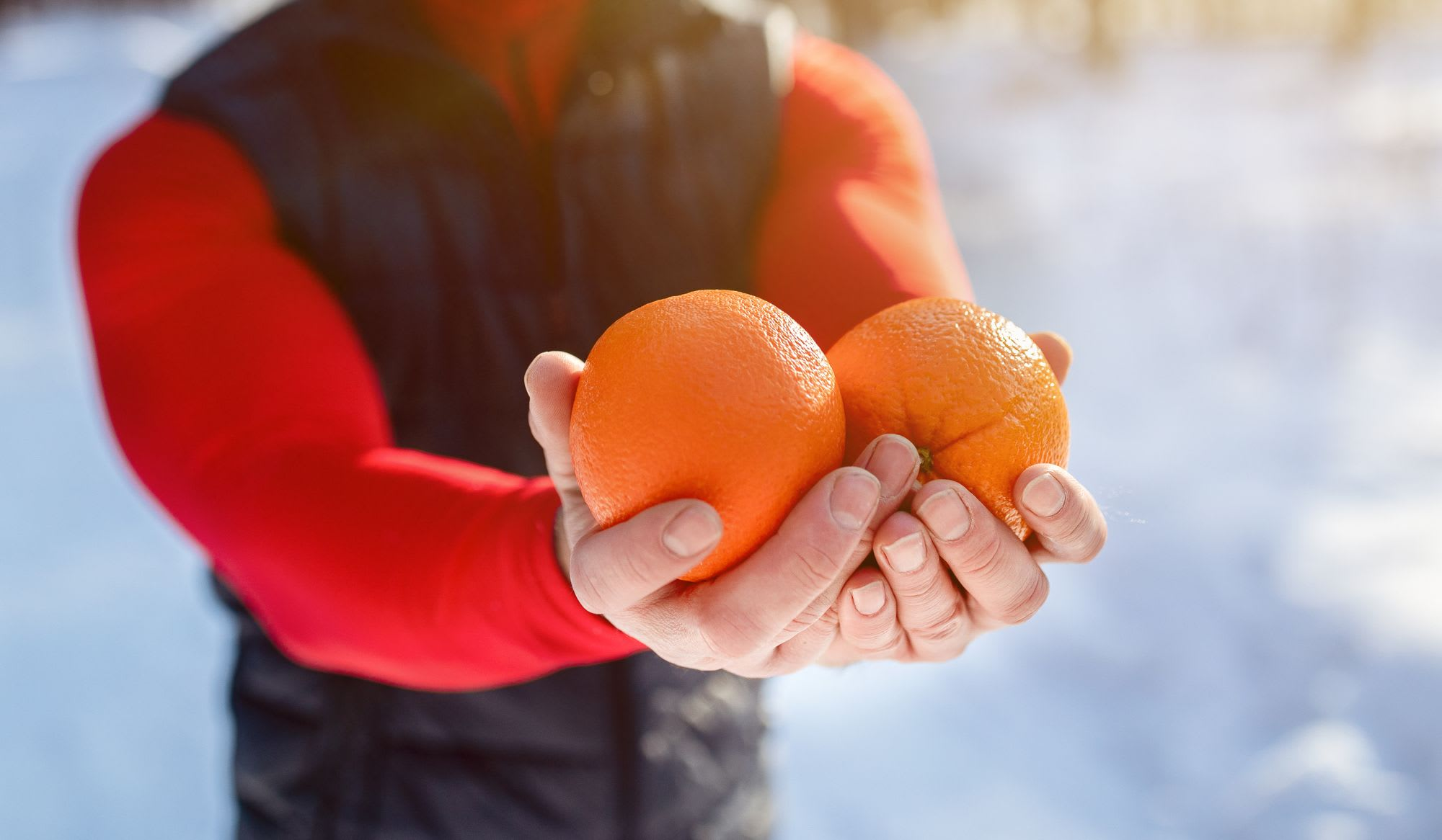 Closeup of fit mature man holding oranges as healthy snack after morning workout at snowy winter