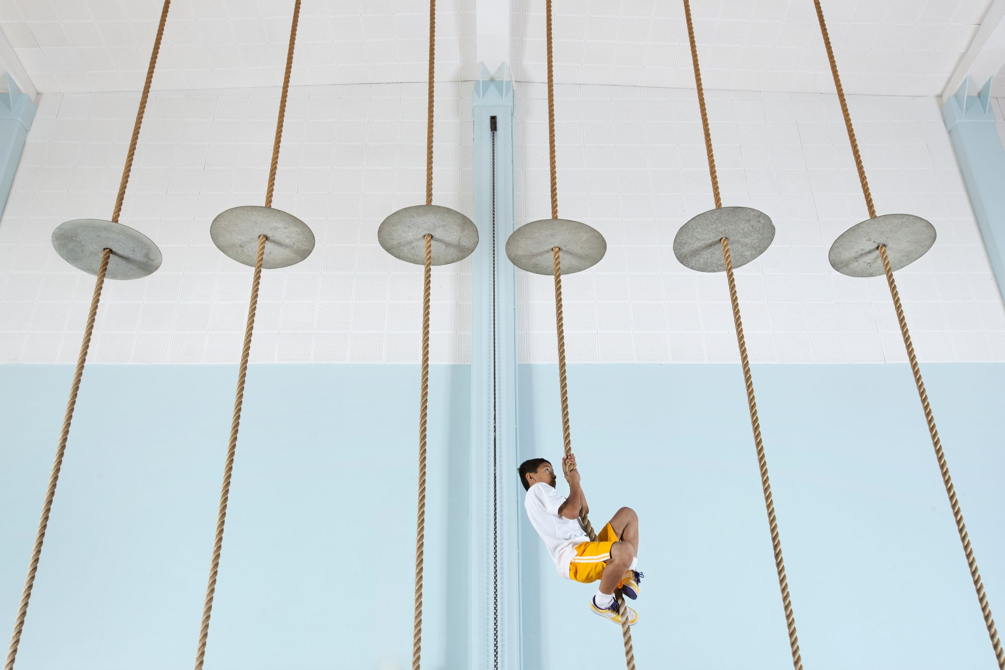 A boy climbing up a rope at the gym.