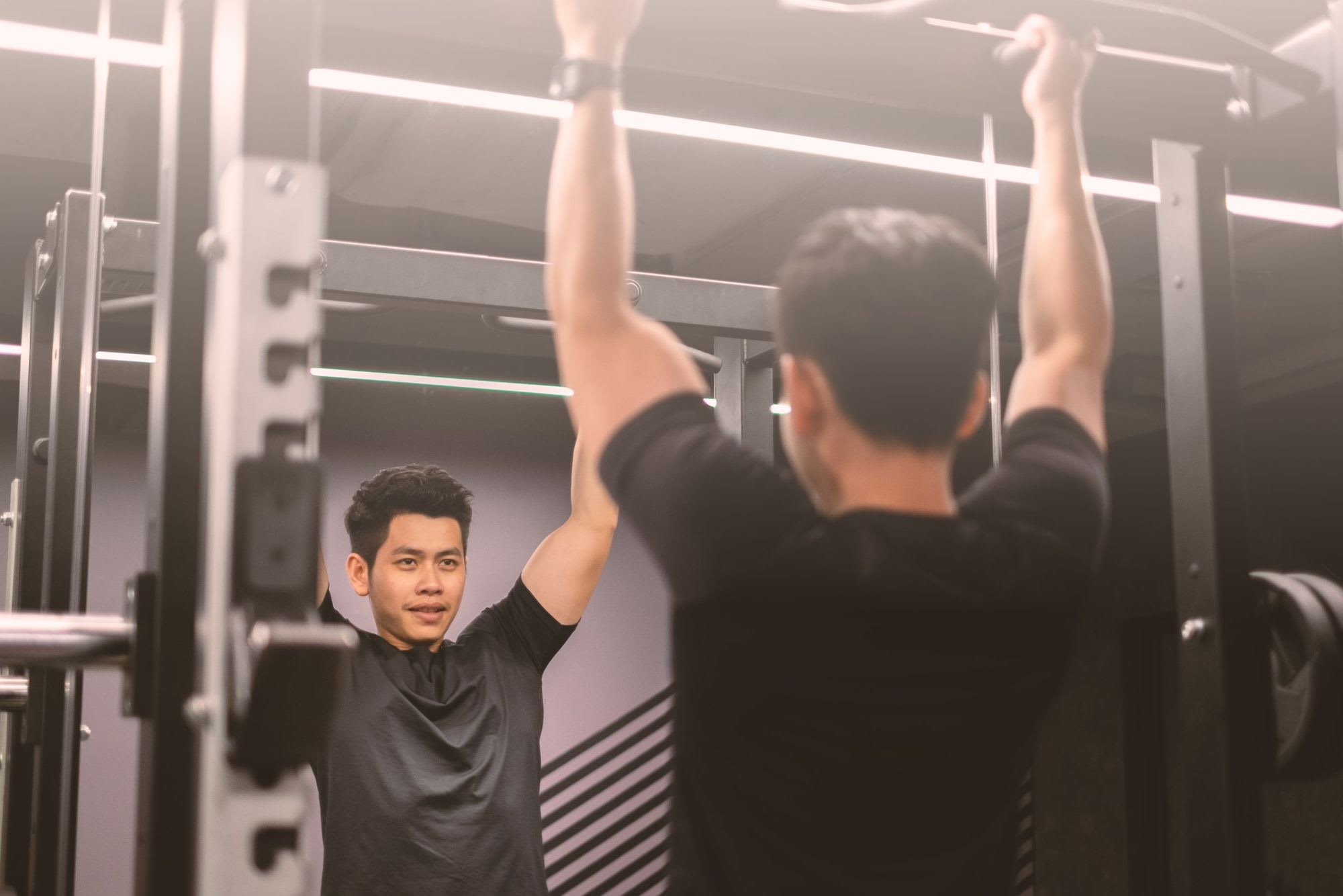 upper section portrait of an asian handsome and healthy man doing strength training in a gym he is