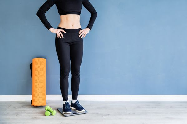 Young content woman in black sport clothes standing on scales