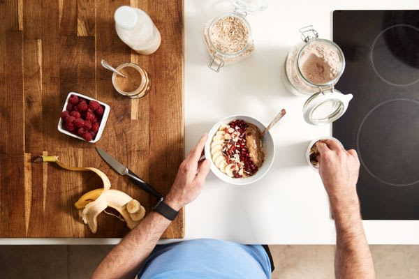 Overhead Shot Of Man Preparing Healthy Breakfast At Home After Exercise