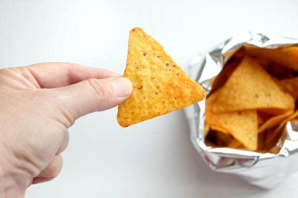 Hand in frame, snacking on corn chips straight out of the bag