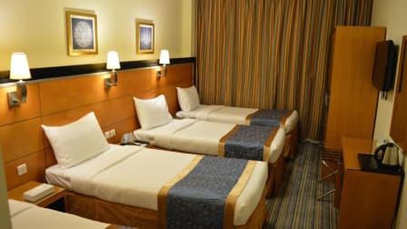 Hotel Al Eiman Taibah quadruple bedroom with 4 single bed with a closet, television and mirror