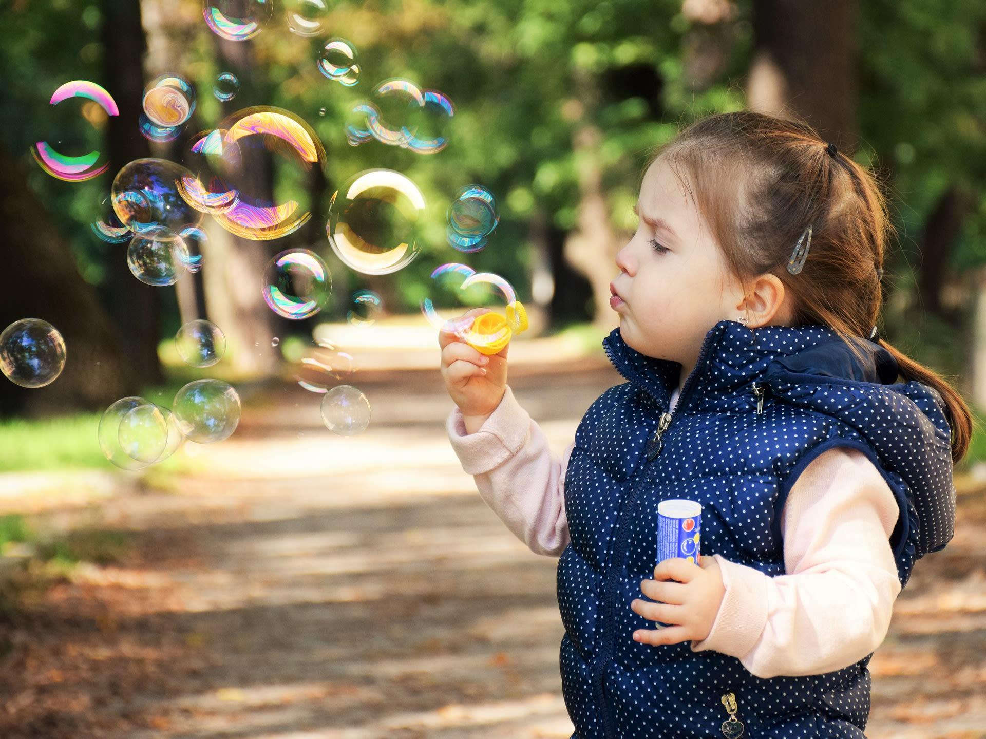 girl playing soap balloons