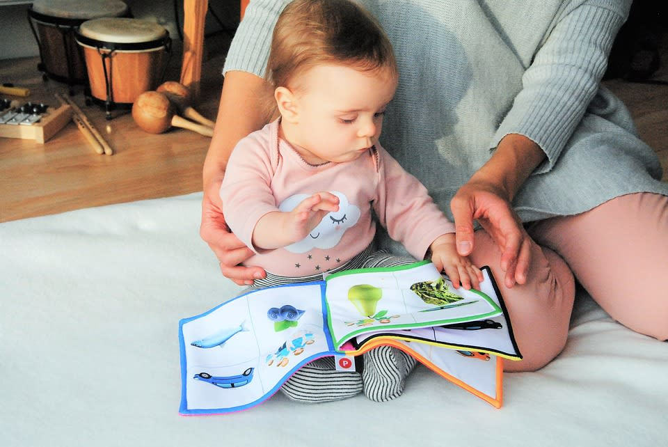 a mother and its baby read a book together