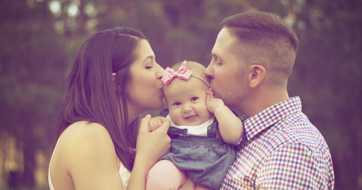 parents kiss a baby