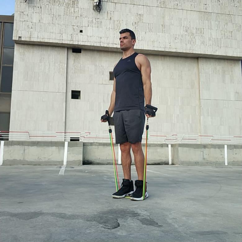 תרגיל הרחקת כתפיים לצדדים בעמידה כנגד גומיה - Standing Lateral Shoulder Raise With Tube Bands