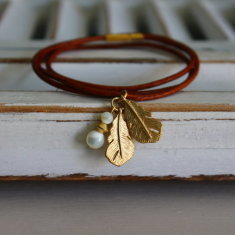 Leather bracelet with gold plated feather charms