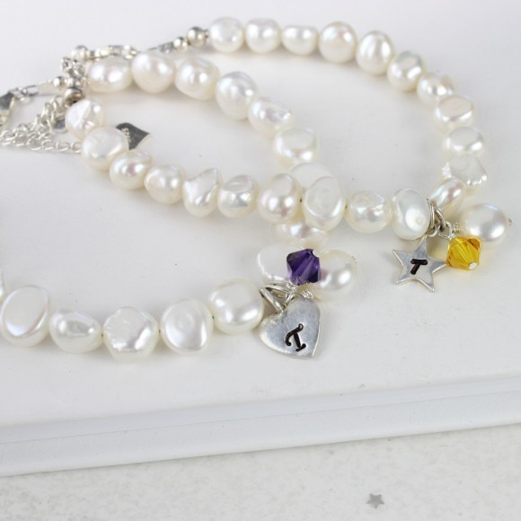 personalised pearl bracelet with purple (heart charm) and yellow (star charm) crystals