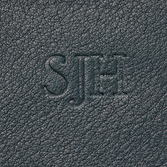 Heat stamped embossed letters (same colour as leather)