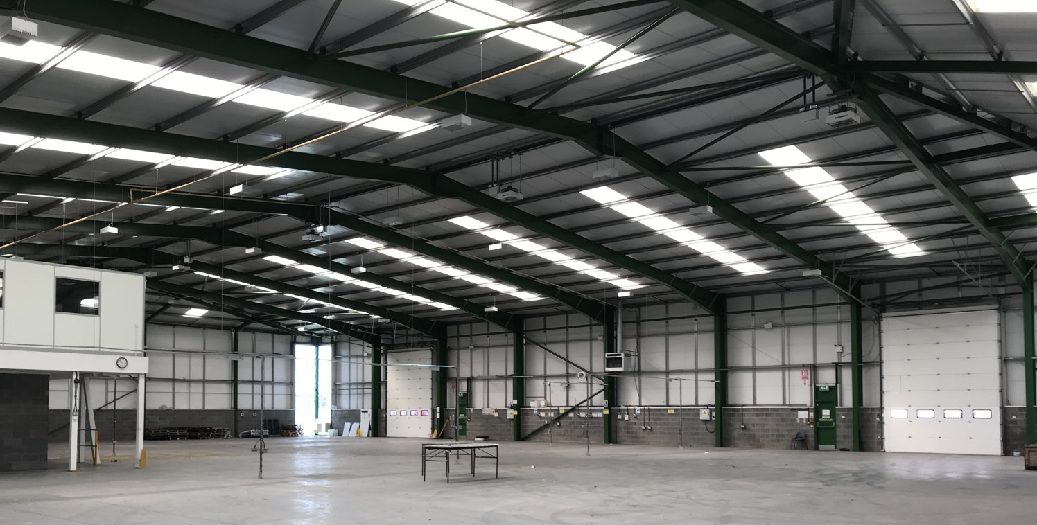 The property comprises a detached high specification steel portal frame industrial unit under a pitched insulated profile metal roof, with insulated metal profile cladding over brick and block walls. Internally the warehouse benefits from concrete fl...